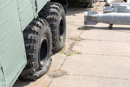 Flat tire of old military heavy truck. General-purpose air bombs on background. Army decay and degradation concept.