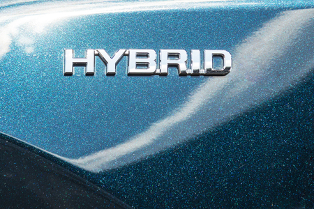 Close-up side view of modern hybrid car. HYBRID symbol on metallic shiny car fender. Green eco energy of future trechnologies