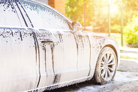 Manual car wash. Washing luxury vehicle with white foamy detergent. Automobile cleaning self service