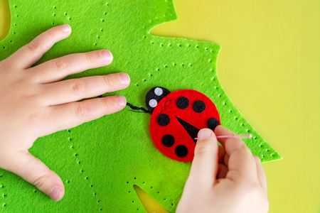 Child making felt soft toy of green leaf and red ladybag . Child DIY activity. Close-up. Children handicraft concept.