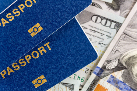 Three biometrical international passports over money background. Blue travel documents lying on US one hundred dollar banknotes. Family tourism and travelling abroad concept