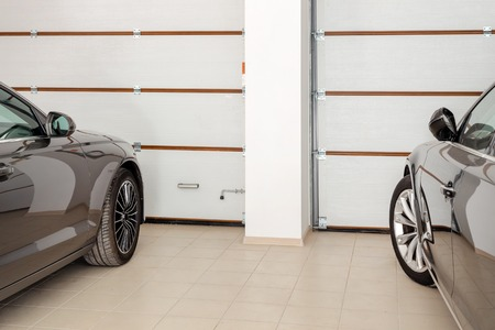 Home garage for two vehicles interior. Clean luxury cars parked at home. Automatic remote control doors. Transport roofed storage. Stockfoto - 103614363