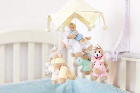 Zbliżenie łóżeczko dziecięce z muzycznym mobilnym zwierzęciem w pokoju dziecinnym. Wisząca zabawka rozwijająca z pluszowymi puszystymi zwierzętami. Szczęśliwe rodzicielstwo i dzieciństwo, oczekiwanie na poród koncepcji dziecka
