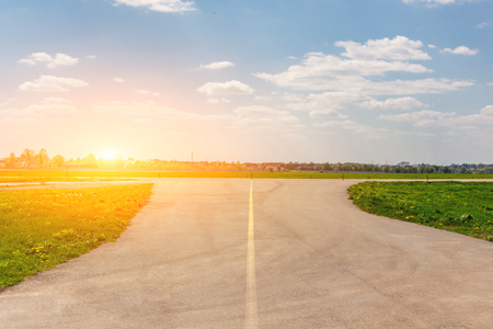 Empty airport taxiway with panoramic blue sky background. Airfield runaway cityscape. Stock Photo