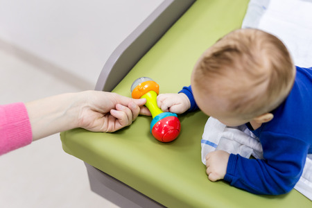 Infant with mother playing on changing table. Mom giving rattle toy to baby boy. View from above.