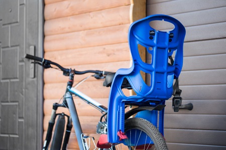 Bike with children carrying seat attached. Cycle with kids transportation equipment stand near wooden garage. Family safety sport activity concept. Banco de Imagens - 106438954