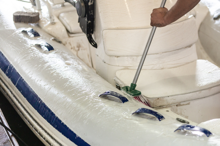 Man washing white inflatable boat with brush and pressure water system at garage. Ship service and seasonal maintenance concept. Standard-Bild