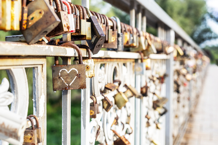 Red heart padlock locked on fence. Lock in shape of heart as symbol of eternal love. Фото со стока