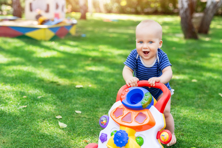 Cute little boy learning to walk with walker toy on green grass lawn at backyard. Baby laughing and having fun making first step at park on bright sunny day outdoors. Happy childhood and concept. Imagens
