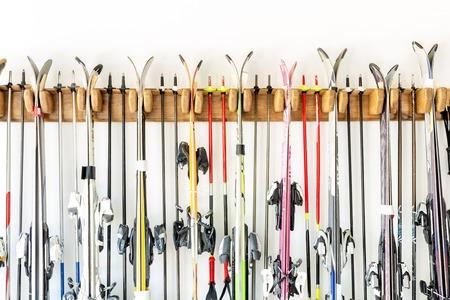 Beaucoup de ski accroché sur un support mural en bois personnalisé au garage pour un rangement saisonnier. Manipulation d'équipements de sports d'hiver extrêmes à l'entrepôt à domicile.