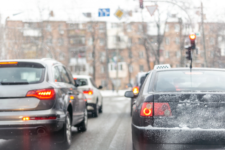 Cars standing in row in traffic jam on city street on slippery snowy road in winter. Vehicles get stuck on road during rush hour at cold winter season. Weather forecast