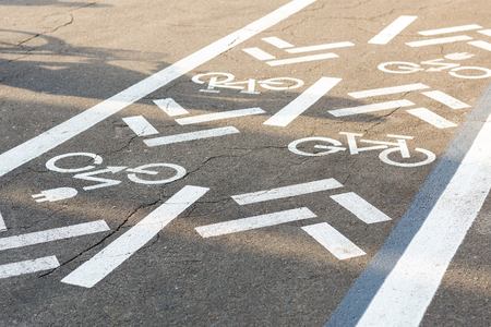 Asphalt road with bicycle and electric transport lane. Cycle and zero emission vehicles white sign on floor. Recreation area for green energy transport in city park.