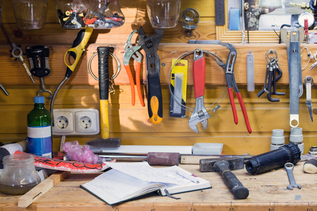 Wooden workbench at workshop. Lot of different tools for diy and repair works. Wood messy table with notebook. Copyspace. Labour day.
