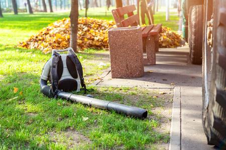 Zware bladblazer liggend op schoon gras in stadspark in de herfst. Seizoensgebonden reiniging en verwijdering van bladeren in de herfst Stockfoto