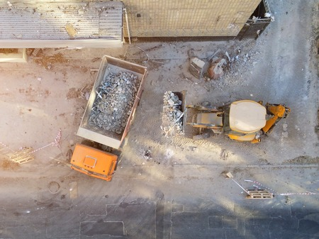 Bulldozer loader uploading waste and debris into dump truck at construction site. building dismantling and construction waste disposal service. Aerial drone industrial background