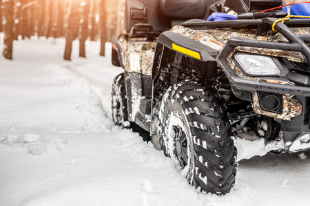 Close-up ATV 4wd quad bike in forest at winter. 4wd all-terreain vehicle stand in heavy snow with deep wheel track. Seasonal extreme sport adventure and trip.
