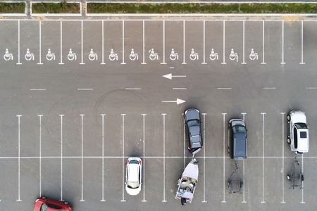 Almost empty outdoor car parking with handicapped symbol icon. Prking places reserved for disabled person. Aerial drone view 免版税图像