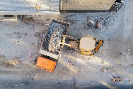 Chargeur de bulldozer chargeant des déchets et des débris dans un camion à benne basculante sur un chantier de construction. service de démantèlement de bâtiments et d'élimination des déchets de construction. Contexte industriel de drone aérien. Banque d'images