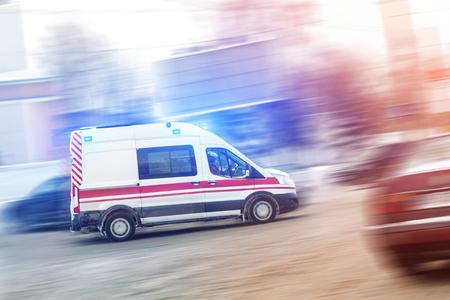 Ambulancia corriendo por el atasco de tráfico de la ciudad en una carretera resbaladiza con nieve fangosa Accidente automovilístico en carretera.