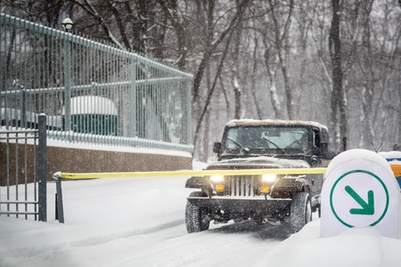 SUV car stopped at automatic entry gate during heavy snowfall. Vehicle access gateway system. Season of Blizzard at winer on city street.