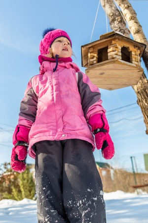 Cute ittle caucasian girl in sport winter jacket having fun playing outdoors with snow. Bird feeder on tree on background. Winter vacation and holidays concept. Children outdoor activities.