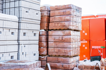 Stock pallets of red bricks wrapped in stretch film at wholesale outdoor market ot store. Construction site with prepared materials.