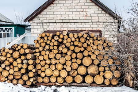Pile of cutted wooden log stacked near house. Firewood timber material stack prepared for heating in winter at old rural building. Stock fotó