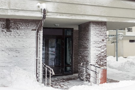 Entrance of modern high-rise apartment building covered with snow and frost after heavy windy snowstorm Snowfall and blizzard aftermath in winter. Cold snowy weather forecast. 免版税图像