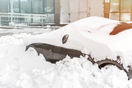 Car on a street covered with big snow layer after heavy snowfall. Extreme blizzard aftermath Archivio Fotografico