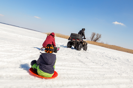 Man on ATV quadbike riding sledges with kids in tow on frozen lake surface at winter. Winter extreme sports and recreation. Children outdoor fun and activities.