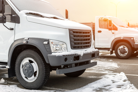 New middle size trucks at dealership parking outdoors at winter. Truck service and maintenance. Delivering and warehouse service. Archivio Fotografico