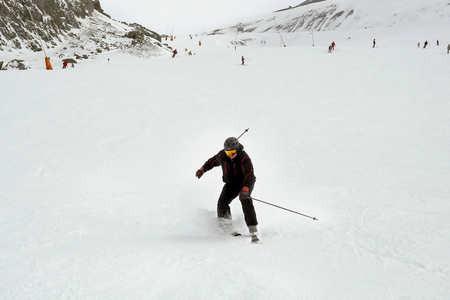 Mature skier fallen during downhill at ski resort in winter. Accident at ski slope due to unfasten ski binding. Extreme winter sport activities. Stockfoto