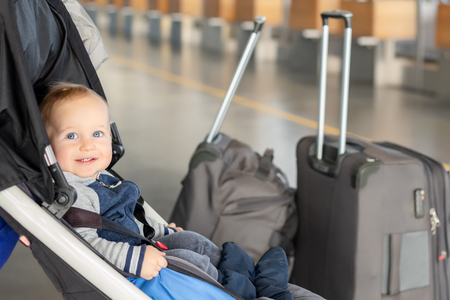 Cute funny caucasian baby boy sitting in stroller near luggage at airport terminal. Child sin carriage with suitcasese near check-in desk counter. Travelling with small children concept.