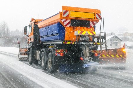 Snowplow truck removing dirty snow from city street or highway during heavy snowfalls. Traffic road situation. Weather forecast for drivers. Seasonal road maintenance