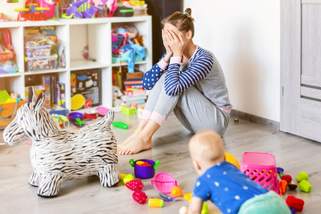 Tired of everyday household mother sitting on floor with hands on face. Kid playing in messy room. Scaterred toys and disorder. Happy parenting