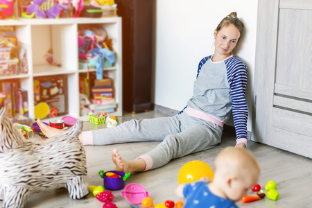 Tired of everyday household mother sitting on floor with hands on face. Kid playing in messy room. Scaterred toys and disorder. Happy parenting Imagens - 116760134