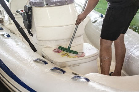 Man washing white inflatable boat with brush and pressure water system at garage. Ship service and seasonal maintenance concept 免版税图像