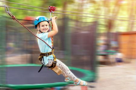 Cute little funny caucasion blond girl in helmet having fun riding rope zipline in adventure park. Children outdoor extreme sport activities concept Banque d'images - 118773756