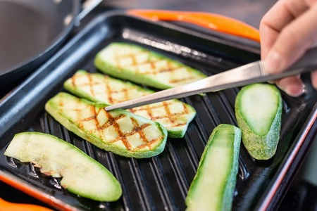 Person hand with tweezers frying organic zucchini on grill iron pan. Close-up grilled sliced vegetables cooking process for vegan snack