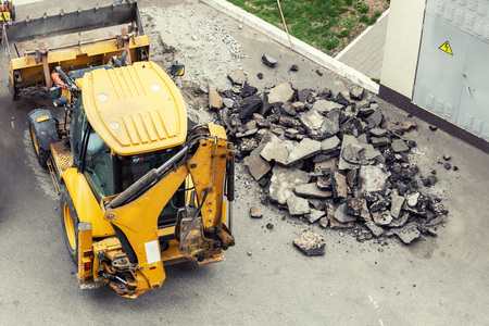 Big jackhammer drill drilling road.Heavy machinery crushing asphalt for stormwater drain repair