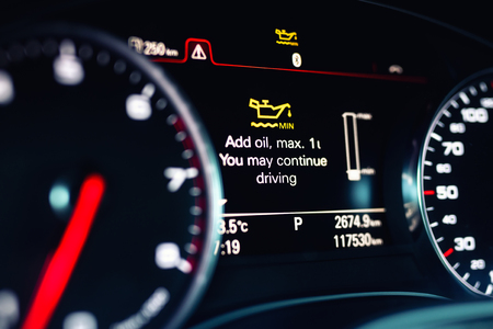 Luxury car color screen dashboard with warning message. Low engine oil level indication. Intelligent Driver Information System