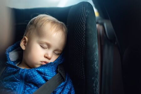 Cute caucasian toddler boy sleeping in child safety seat in car during road trip. Adorable baby dreaming asleep in comfortable chair during journey in vehicle. Children care and safety on roads. 免版税图像