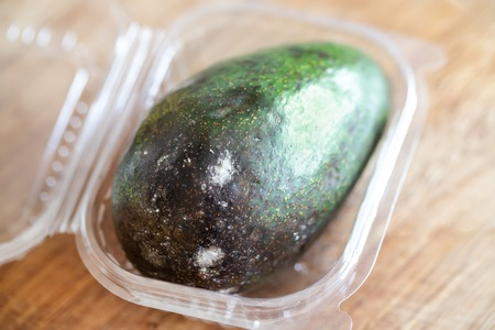 Close-up spoiled avocado in plastic box on wooden background.
