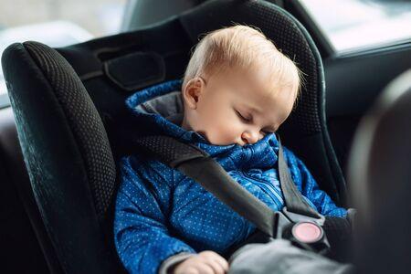 Cute caucasian toodler boy dormant dans un siège de sécurité pour enfant en voiture pendant un voyage sur la route. Adorable bébé rêvant endormi dans un endroit confortable pendant le voyage en véhicule. Soins et sécurité des enfants sur la route. Banque d'images