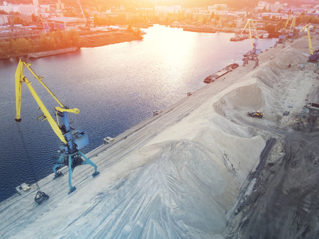 Aerial view of heavy crane loading bulk goods at Dnieper river cargo port terminal in Kiev at  evening sunset time. Industrial inland navigation. Stockfoto