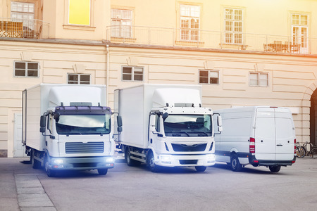 Different small and medium courier service  trucks and van at building courtyard. City delivery cargo shipping company vehilcles parked at street. Stockfoto