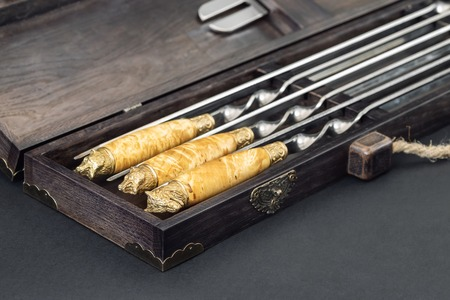 Close up handles Big luxury stainless steel skewers set in wooden box for grill and barbecue. Expensive high quality exlusive gift for man hunter.