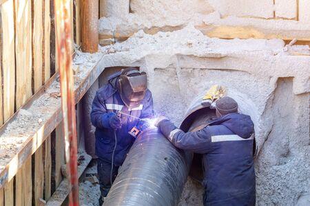 Lasser lassen water of gas stalen pijpleiding met assistent werknemer in greppel. Stadsondergrondse nutsbedrijven vernieuwing en vervanging, Stockfoto