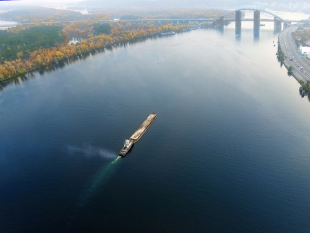 Scenic aerial cityscape of Kiev and river Dnipro at sunset. Tugboat supporting barge with sand bulk materials heading down river Dnieper. Ukrainian inland navigation and river freight cargo.