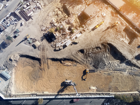 Construction site aerial view. Mall building base with solid concrete pillars. Heavy machinery piling and high tower crane working. Industrial aerial background.